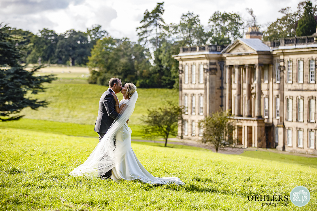 beautiful shot in the sunshine as the couple kisses with the fascade of Calke Abbey in the background