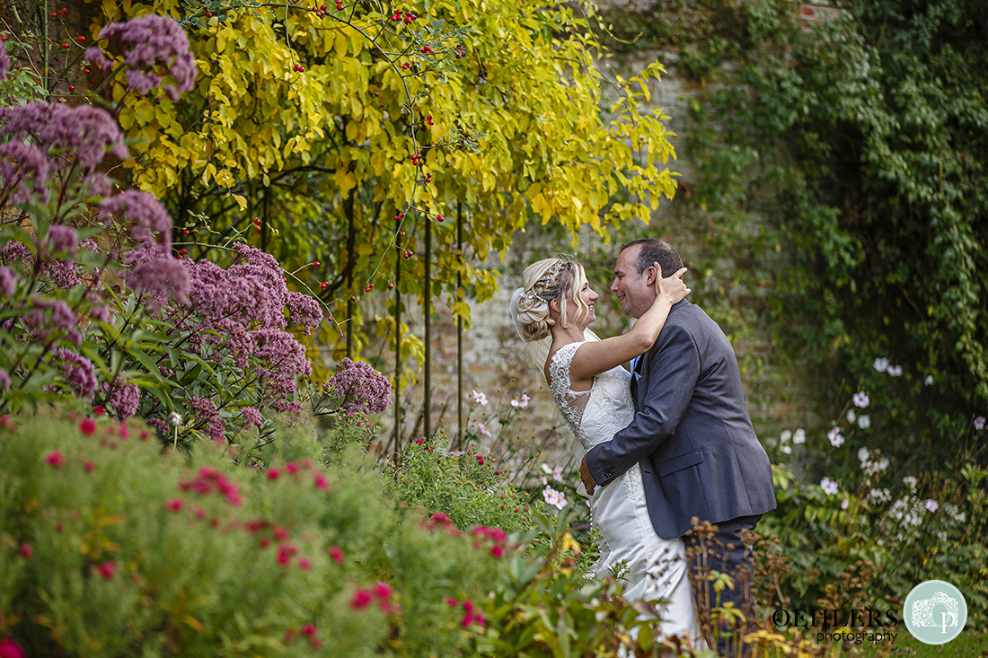 bride and groom stealing a moment together in the gardens at Calke Abbey