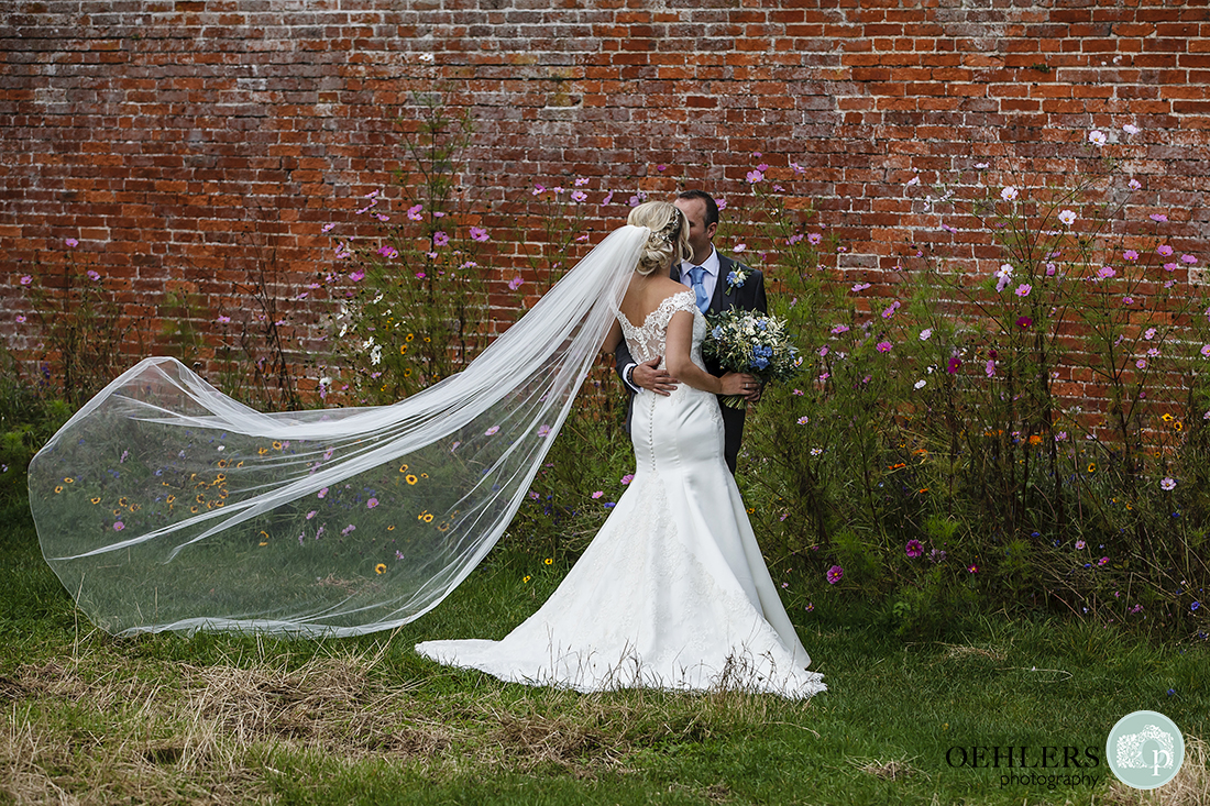 couple stealing a kiss with the veil blowing in the breeze