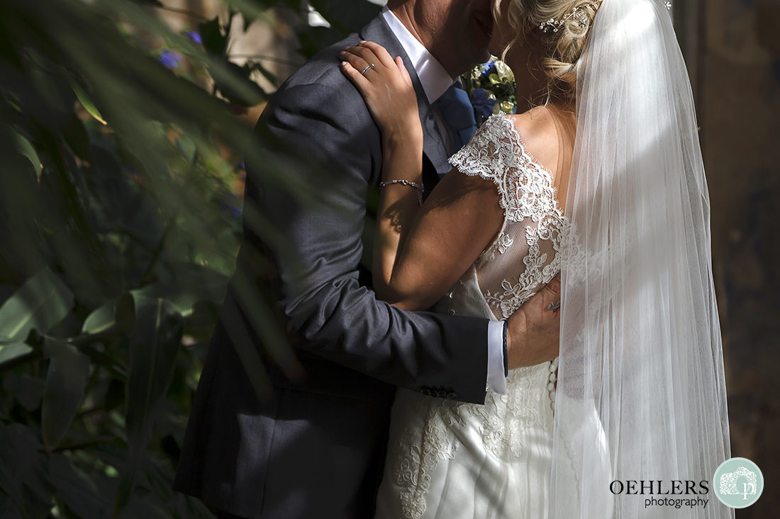 close up of couple's torsos as they hug and kiss showing the detail on the bride's dress