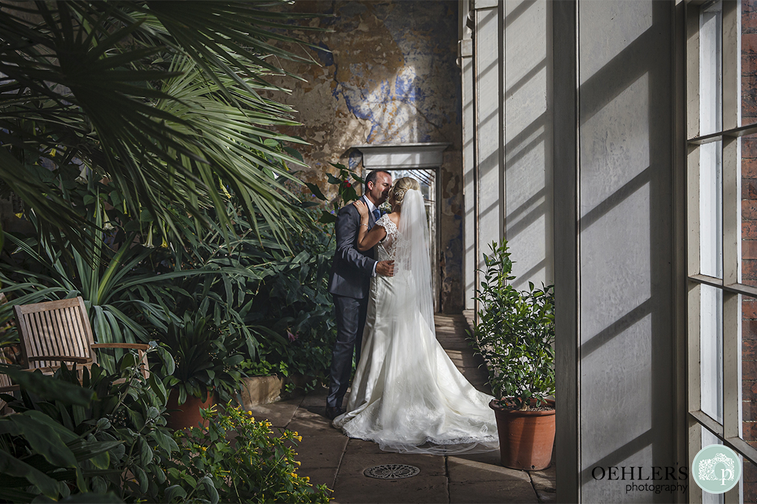 bride and groom stealing a moment in the orangery at Calke Abbey