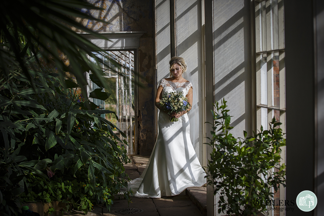 bride looking down at her bouquet whilst leaning against a pillar in the orangery
