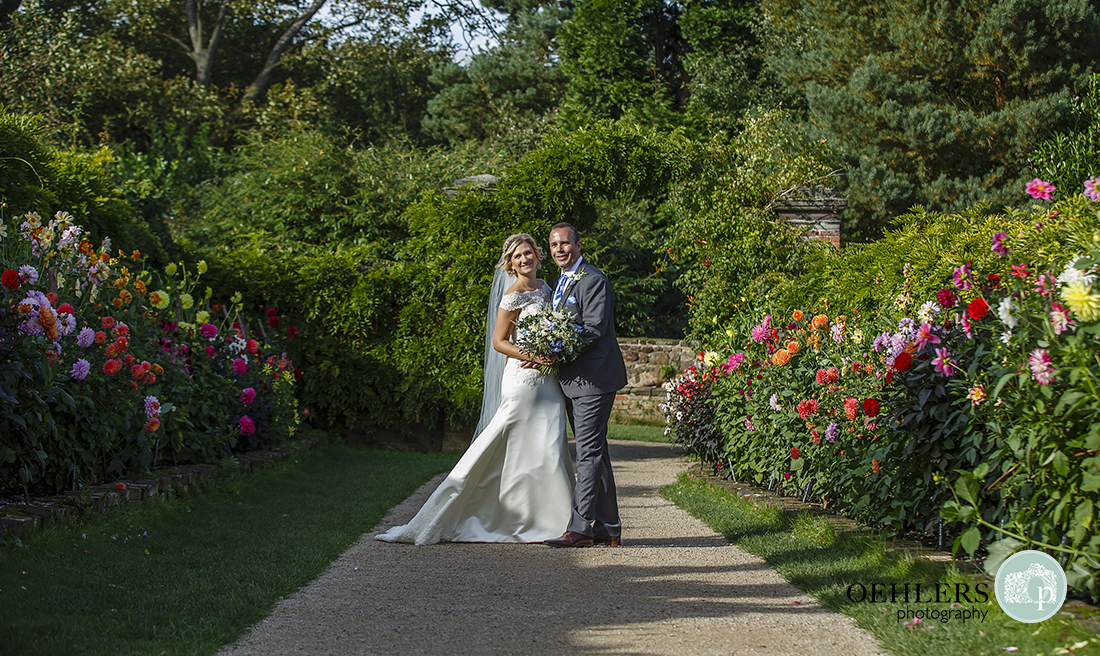 couple portrait in the middle of a pathway bordered by colourful flowers