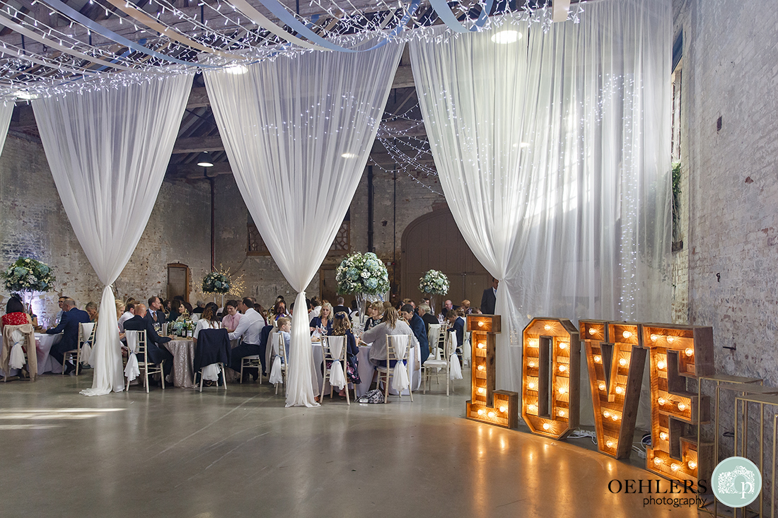 elegant wedding breakfast area adorned by fairy lights and voiles with love sign to the right