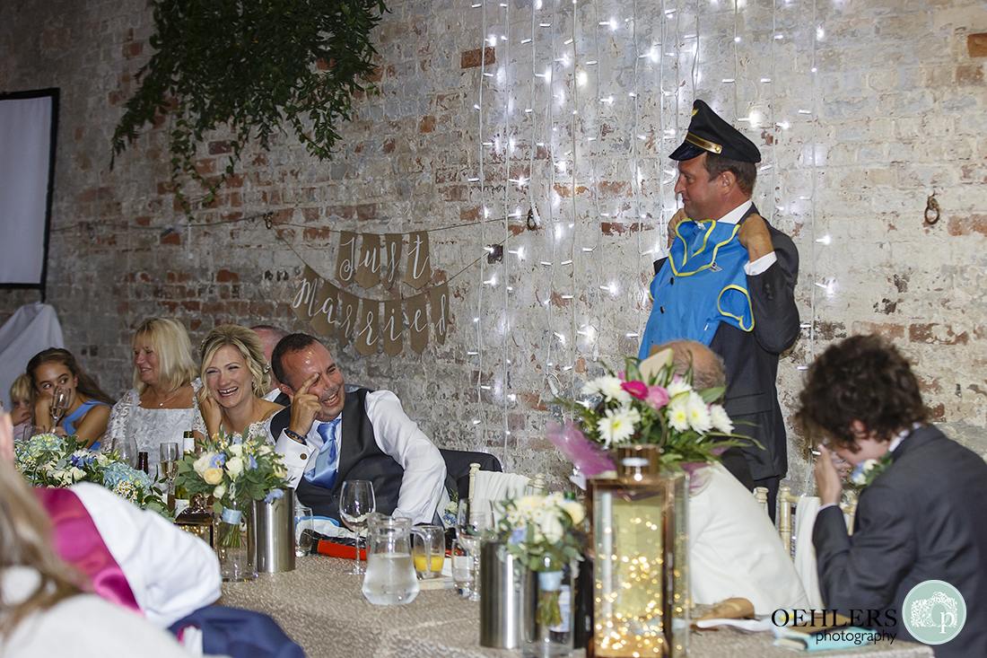 bestman shows the guests, during his speech, the air hostess outfit the groom wore on his stag do
