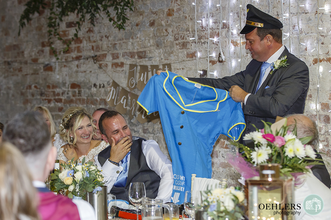 groom and bride laughs at bestman's speech as he holds up outfit the groom wore for his stag do.