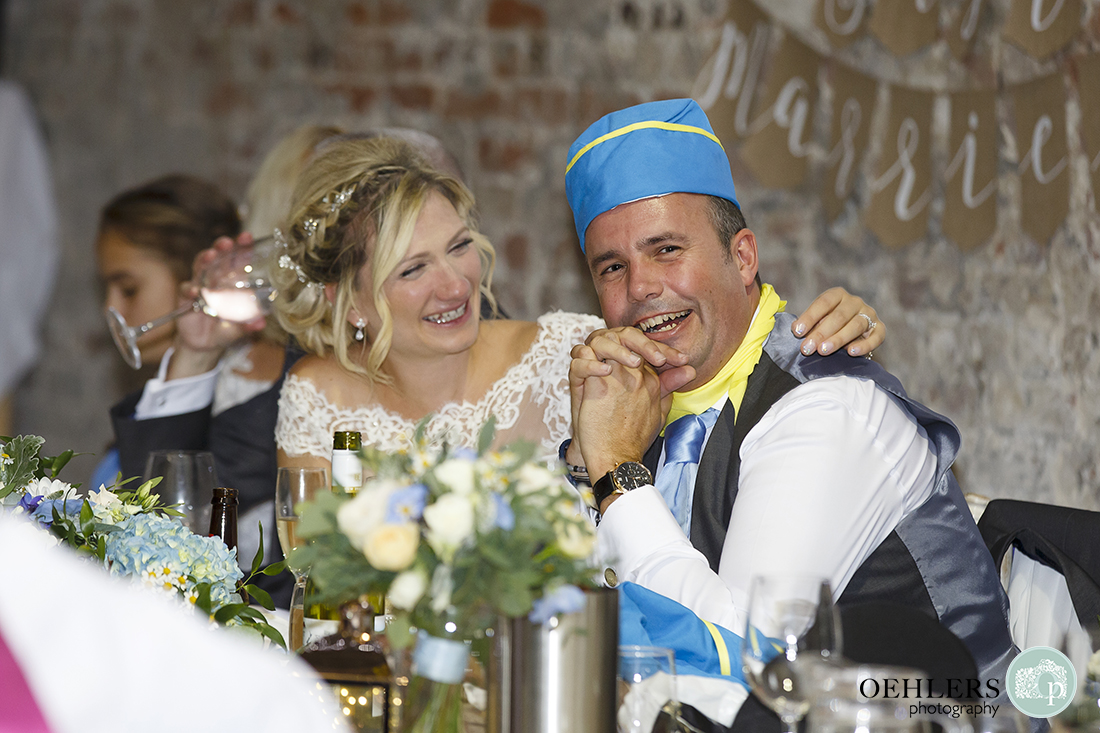 bride puts her arm around embarrassed groom wearing an air hostess hat during the speeches