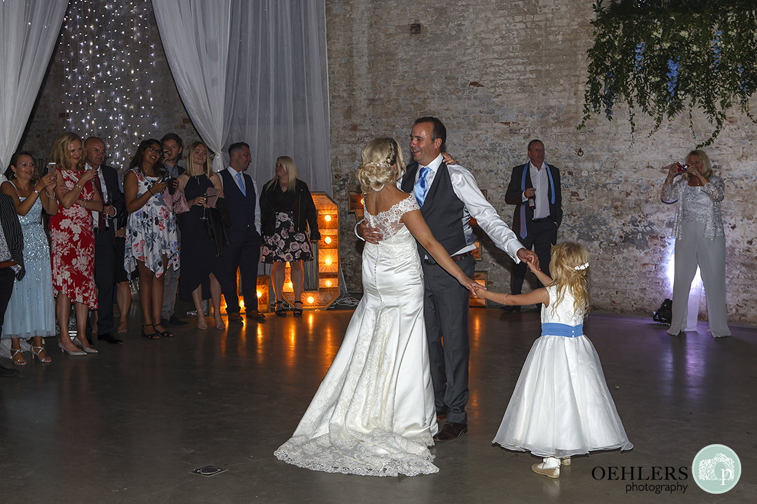 guests gather to watch the first dance with the couples' young daughter holding their hands