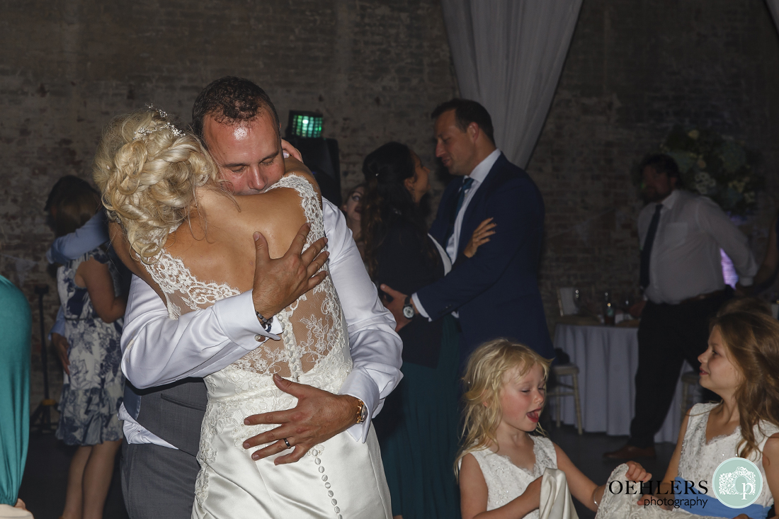 close up of the groom giving the bride a huge hug whilst dancing together