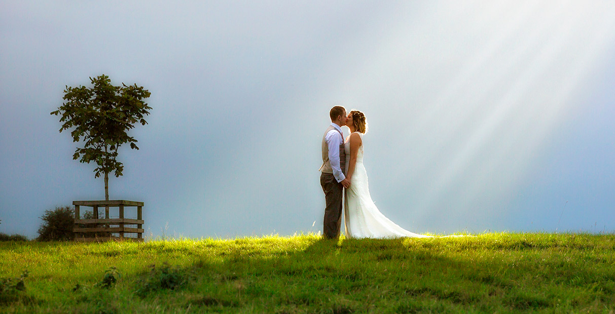 Nottingham Wedding Photographers-Couple in a field lit by the sun's rays