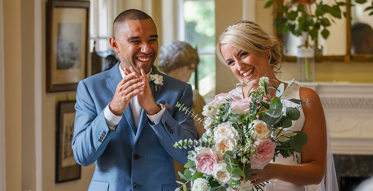 Nottingham Wedding Photographers-A happy couple applauding their guests after the wedding ceremony