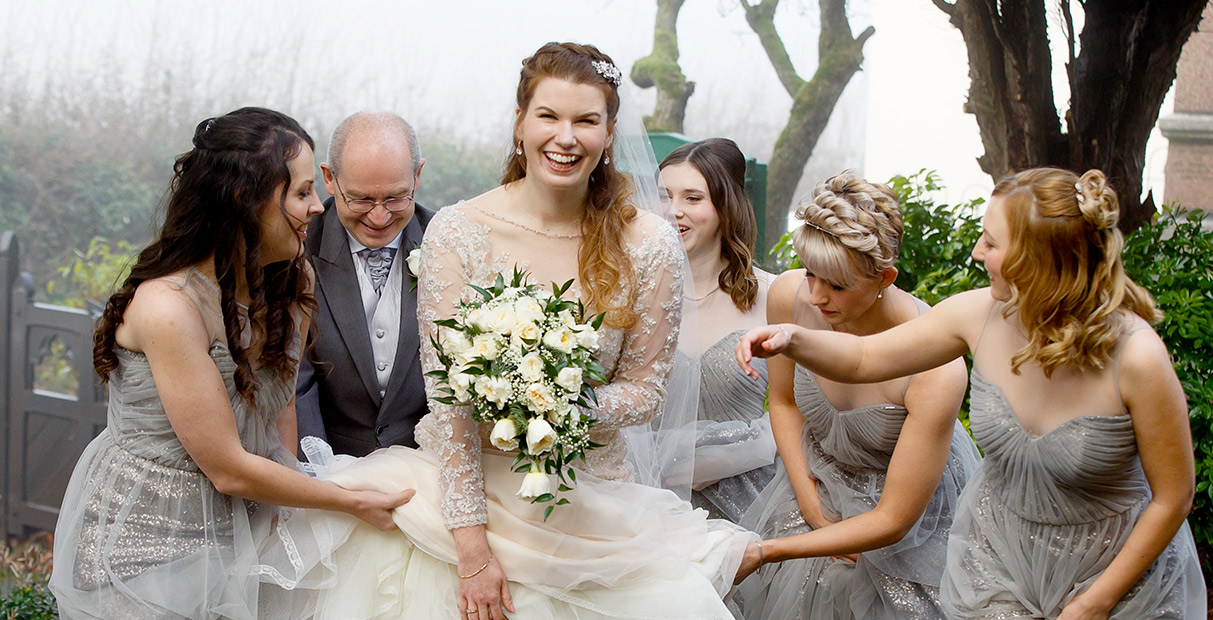 Bride with bridesmaids and dad as she walks towards the church