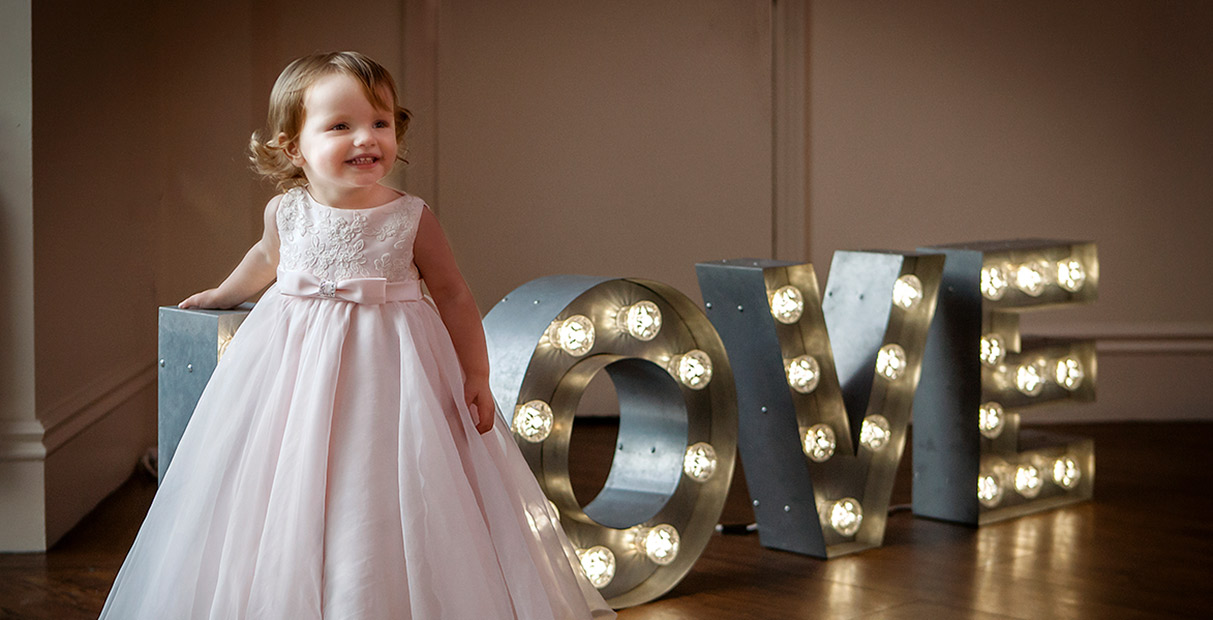 Nottingham Wedding Photographers-Cute flower girl in front of Love Sign