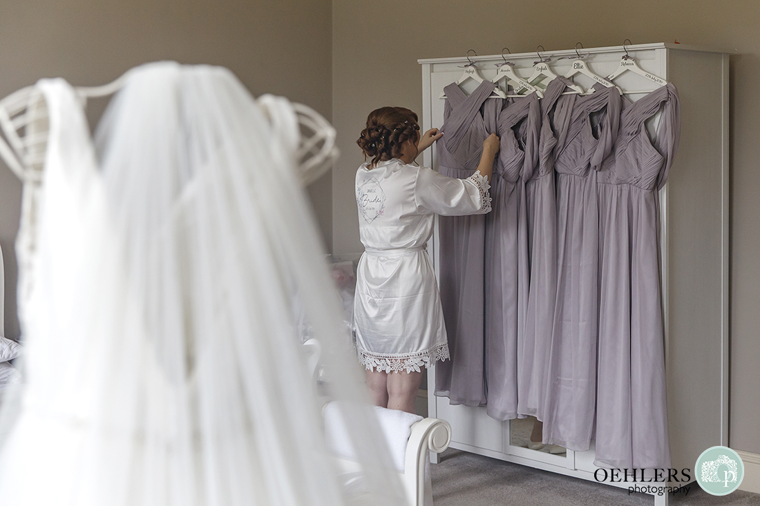 Bride in dressing gown adjusting her bridesmaids dresses hanging on a cupboard
