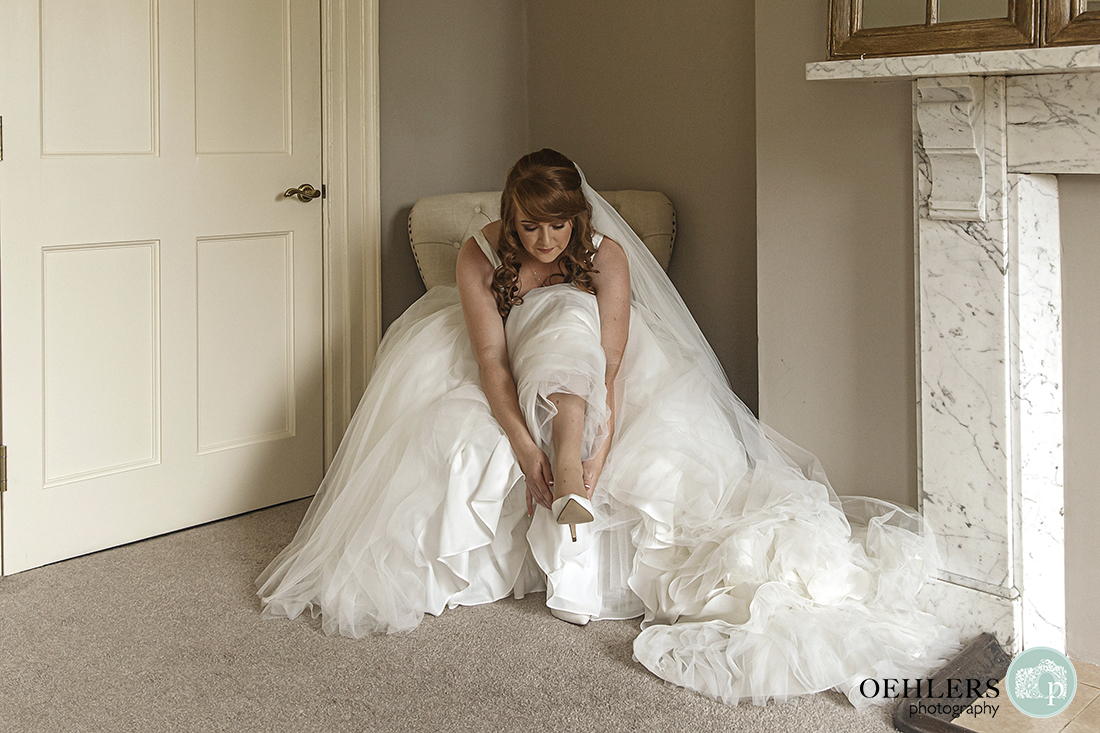 Beautiful photo of the bride leaning forward in her dress to put on her shoe