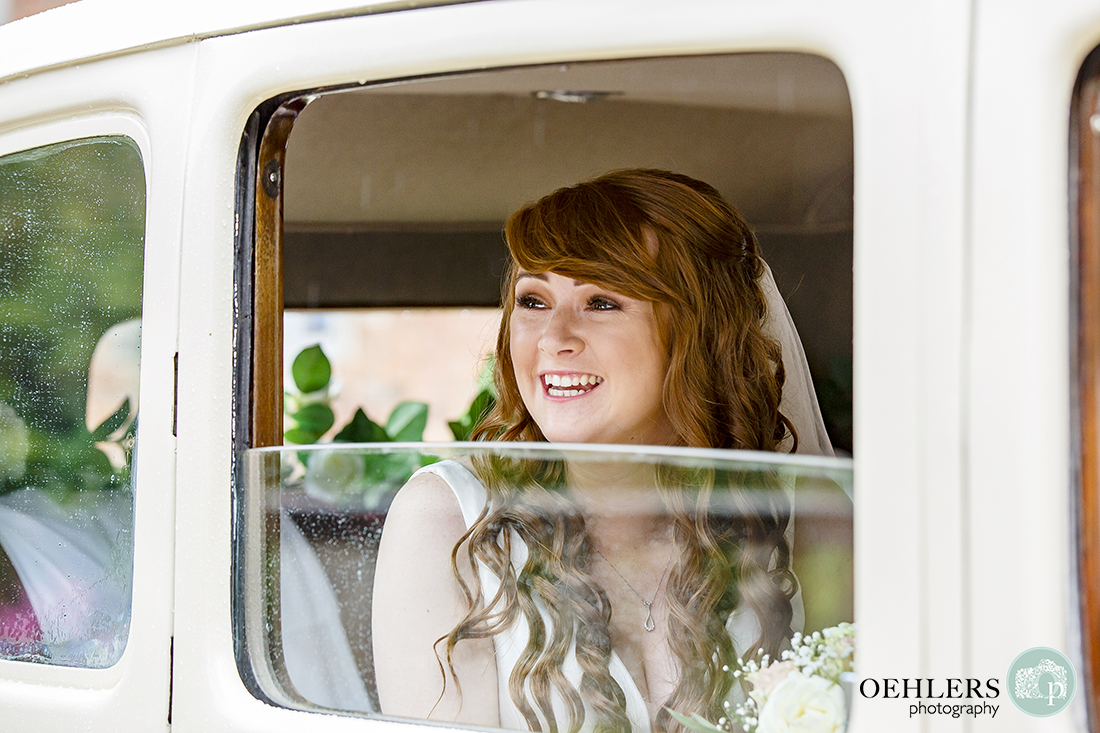 Bride looking happy as she looks out of the window of her wedding car.