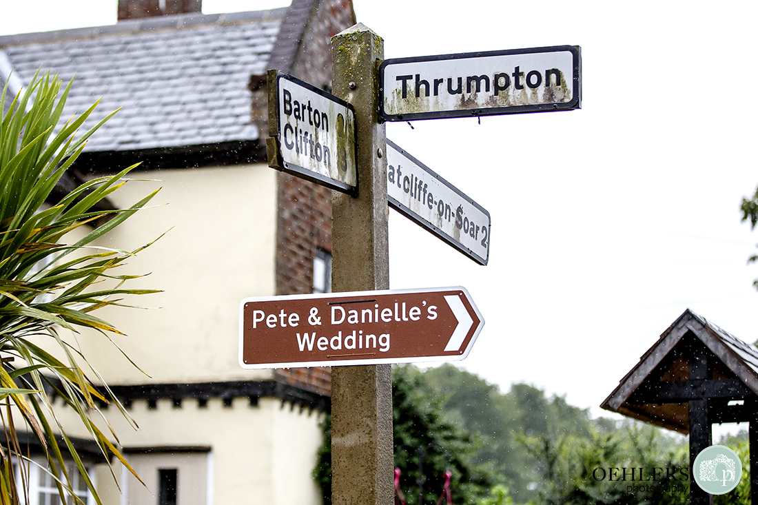 A brown sign on a signpost that says Pete & Danielle's Wedding