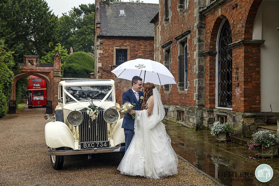 Bride and Groom under their umbrella in front of their car and in front of a rainy Thrumpton Hall