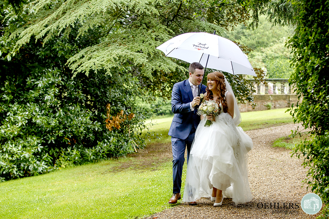 Bride having a giggle with her groom whilst walking under their umbrella to the marquee at Thrumpton.