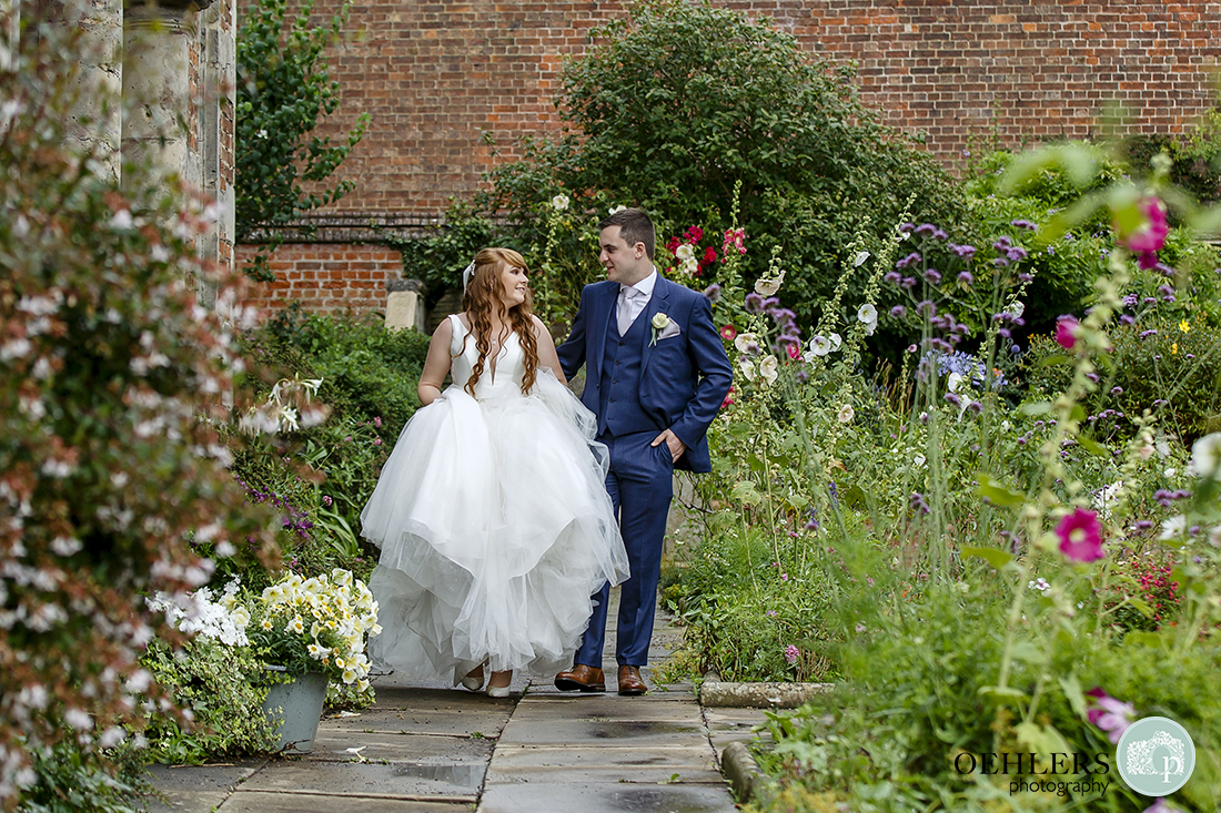 Bride looking at her Groom whilst walking through the rose garden of Thrumpton Hall.