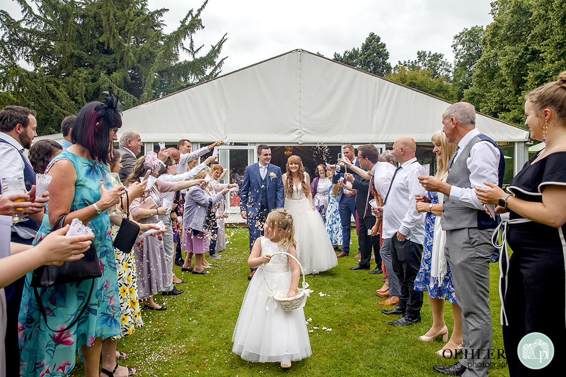 Confetti line outside the marquee whilst the flowergirl leads the bride and groom with a basket of confetti.