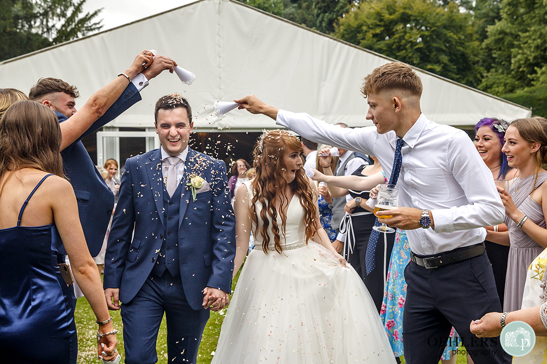 Two of the guests in the confetti line tipping their cone full of confetti onto the groom's head.