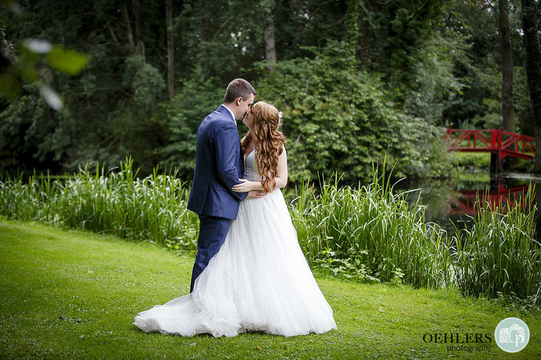 Beautiful, romantic photo of the bride and groom kissing by the lake at Thrumpton Hall