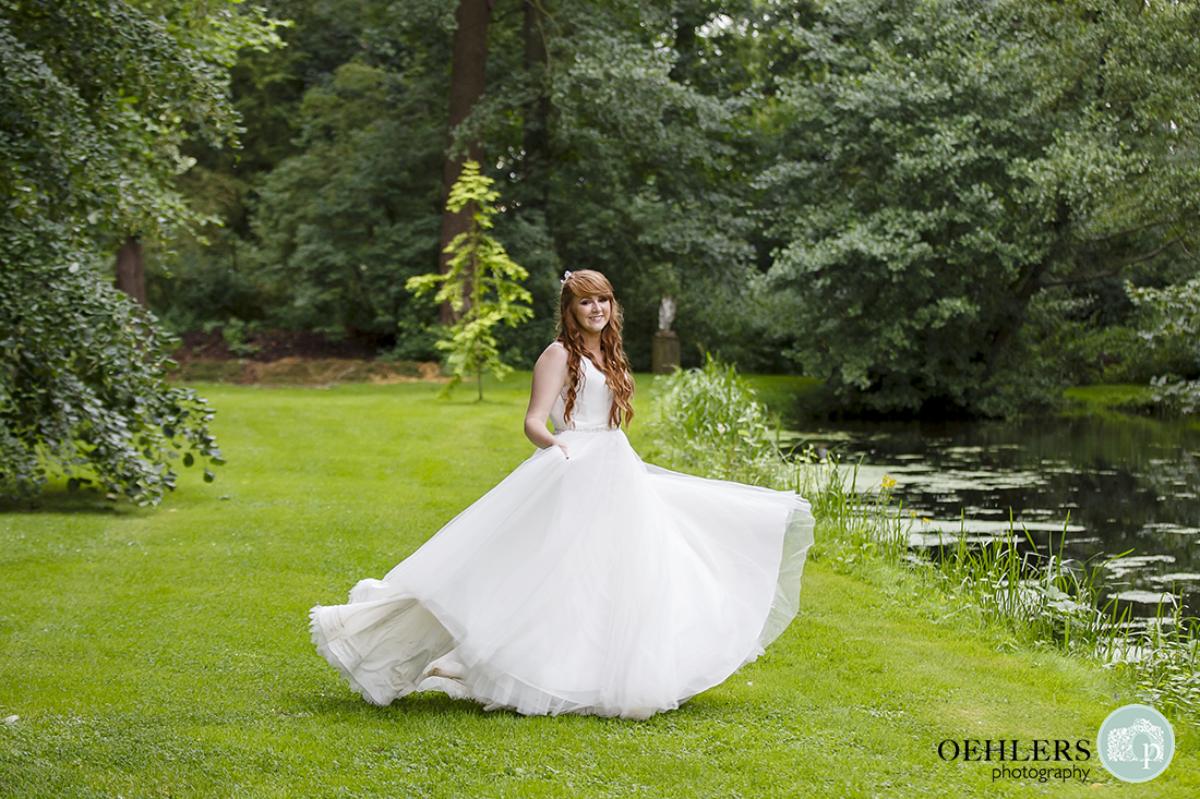 Picture of the bride swirling her dress by the lake at Thrumpton Hall.