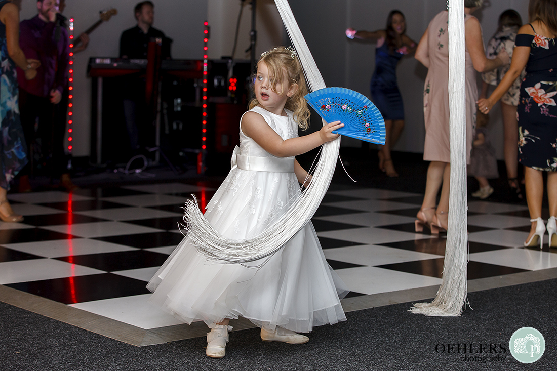 Flowergirl with a blue hand fan playing amongst the drapes of the dance floor.