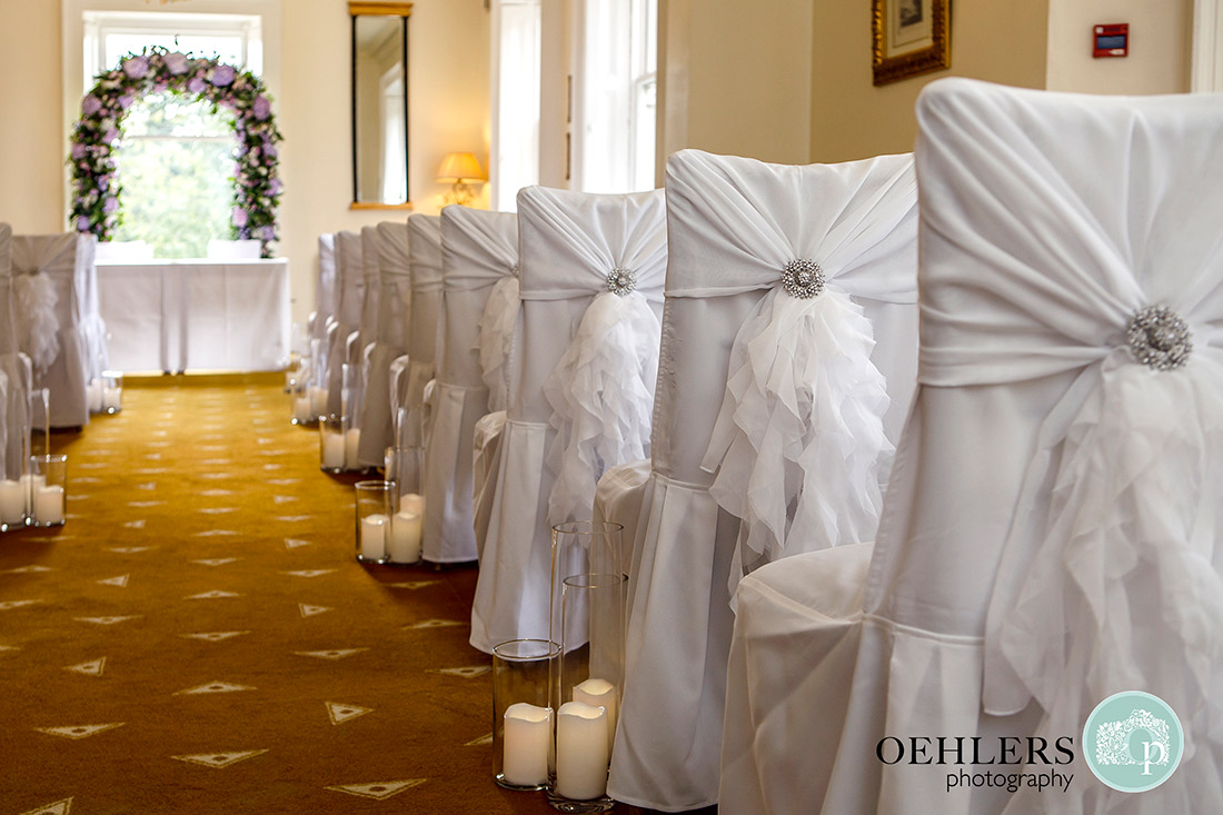 Frilly chair dressings with jewel brooches in the ceremony room.