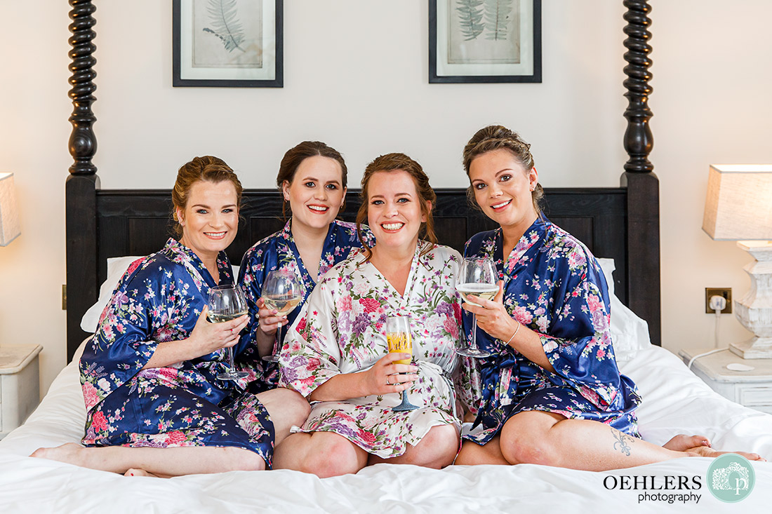 Bride and her bridesmaids on the bed in dressing gowns.