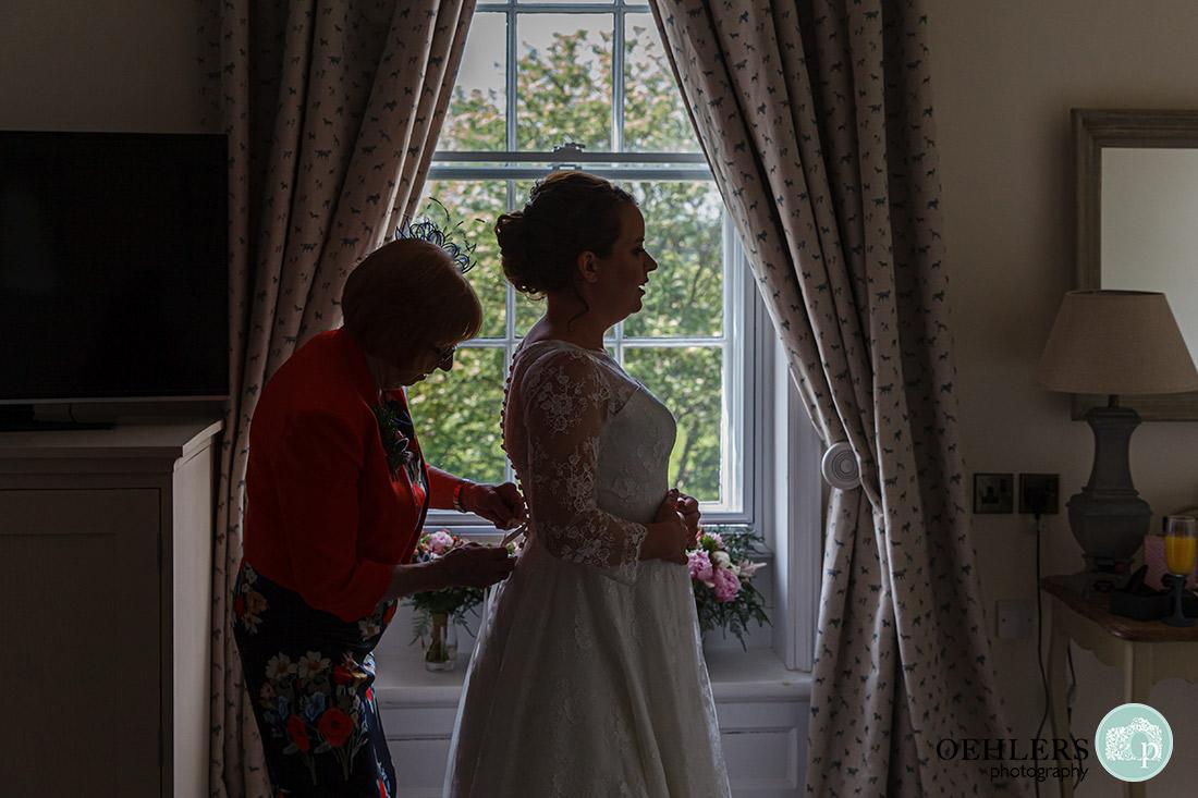 Mum helping her daughter into her wedding dress.