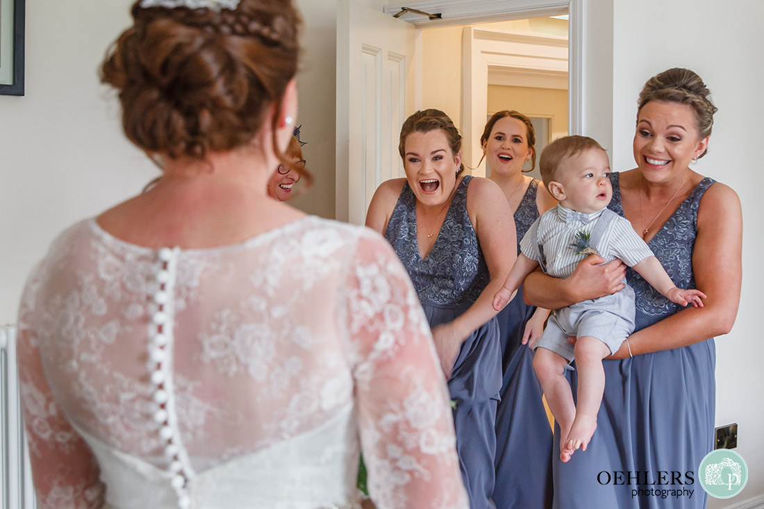 Emotional bridesmaids seeing their bride for the first time in her dress.