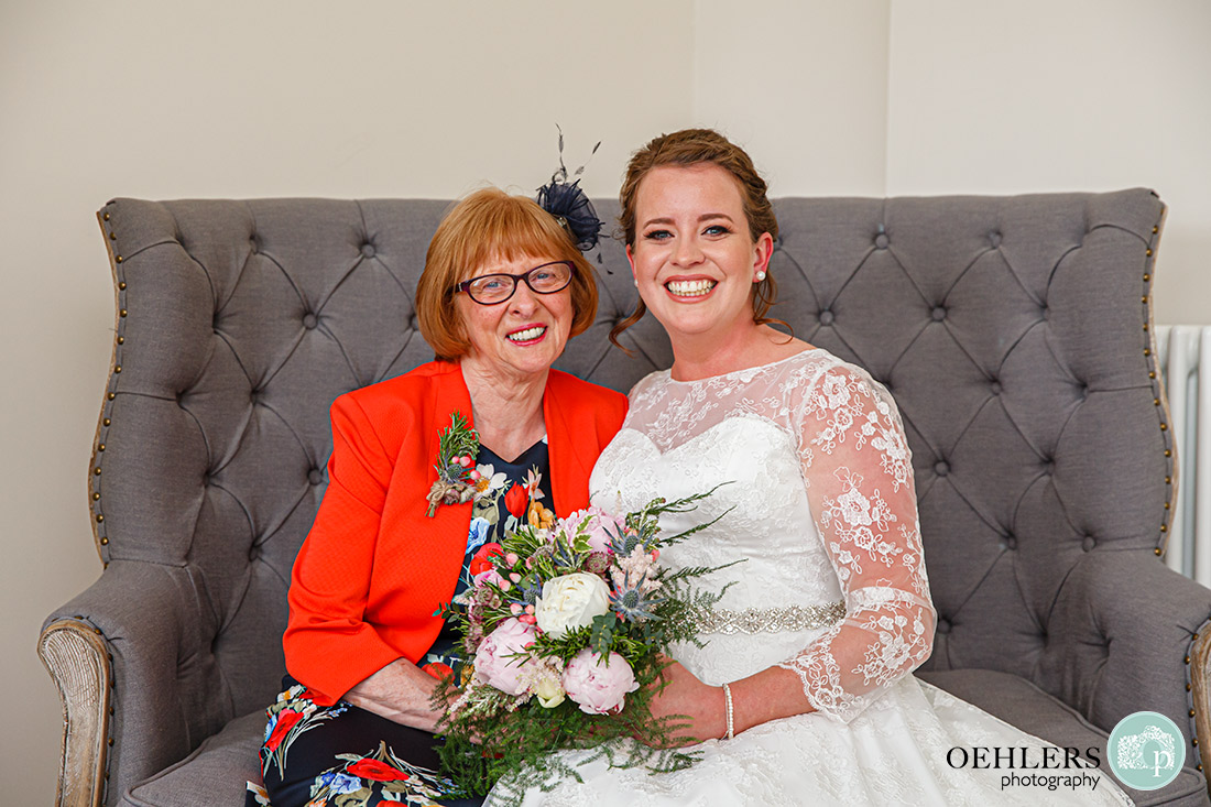 Posed photo of mum and bride sitting on the sofa in the bridal suite.