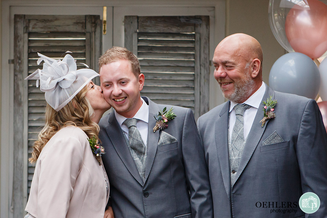 Mum kissing the groom on his cheek as dad looks on.