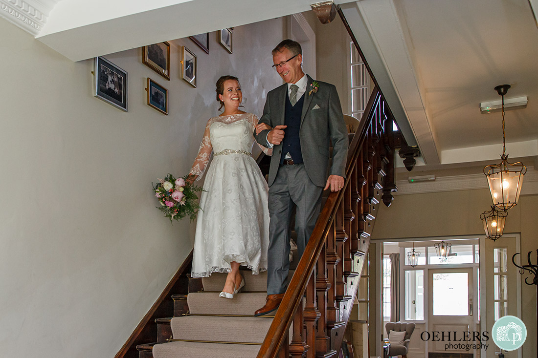 Kedleston Country House Photographers - bride and good friend walking down the stairs.
