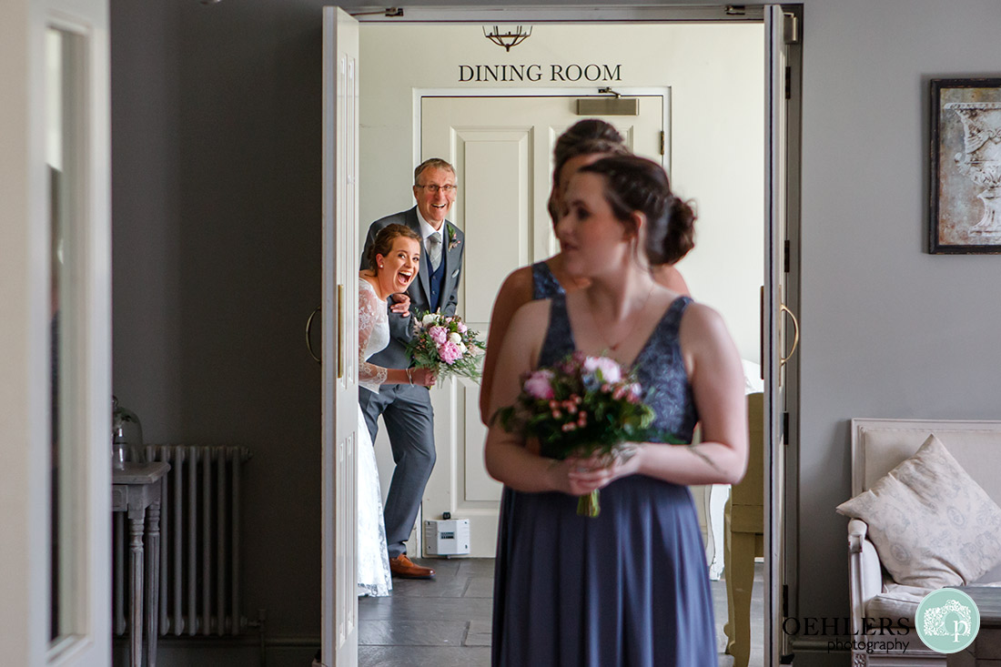Kedleston Country House Photographers - bride and firend appearing around the corner.