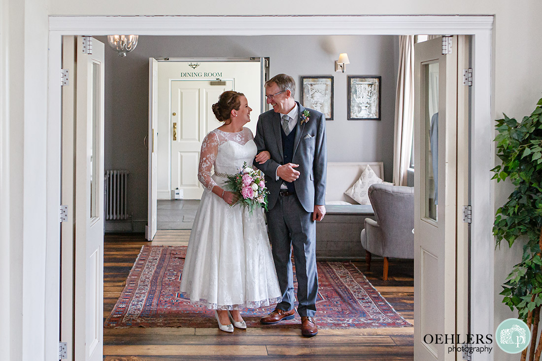 Kedleston Country House Photographers - bride and friend looking at each other before they walk down the aisle to the groom.