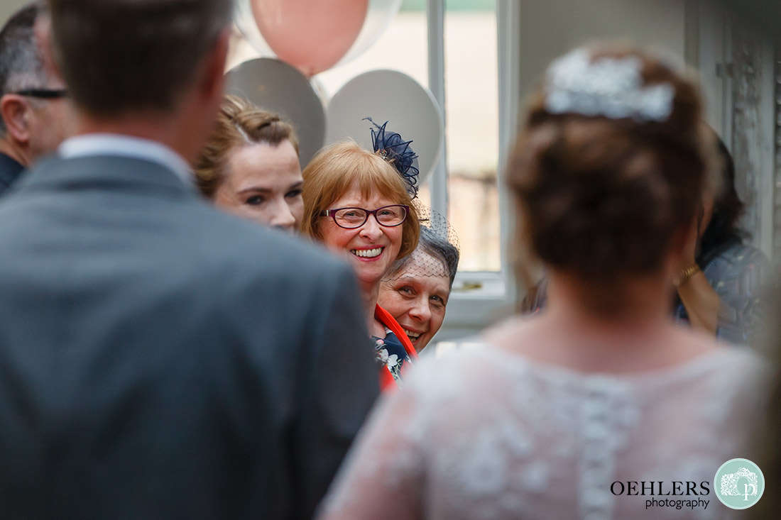 Kedleston Country House Photographers - mum and friends looking at the bride as she walks down the aisle.
