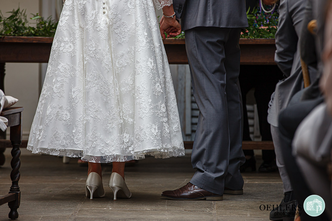 Kedleston Country House Photographers - photograph of the bride's bottom of dress and groom's shoes.