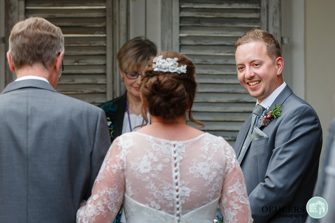 Kedleston Country House Photographers - groom close to tears as he sees his bride for the first time.