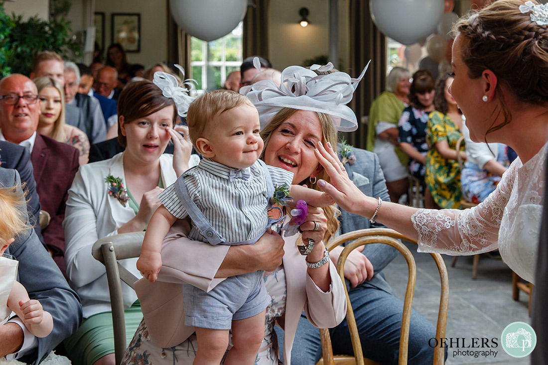 Kedleston Country House Photographers - bride doing a 'high-five' with their son.