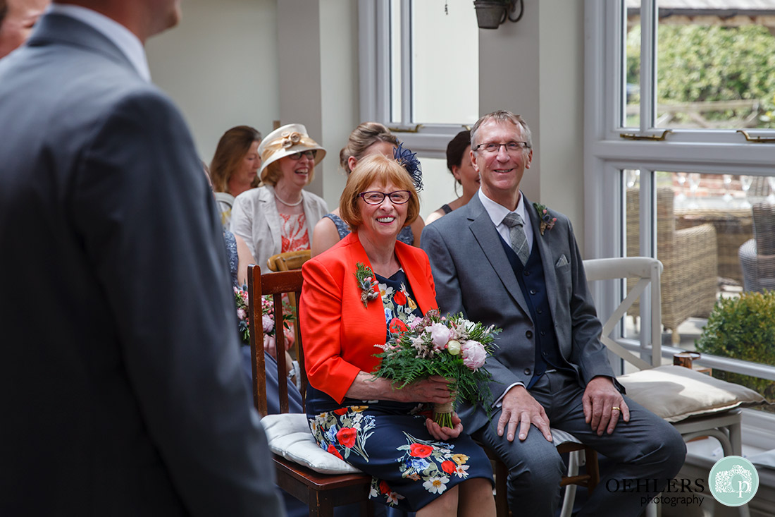 Kedleston Country House Photographers - guests looking at the couple being married at the ceremony table.