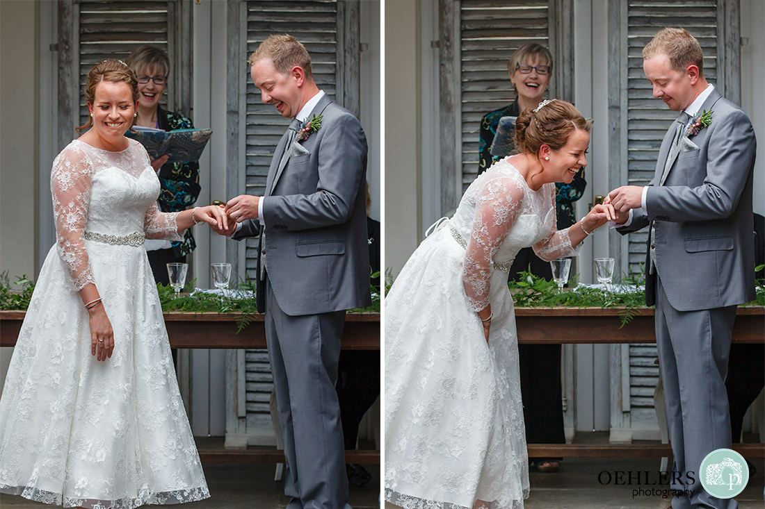Kedleston Country House Photographers - Bride in stitches as groom finds it difficult to put on her wedding ring.