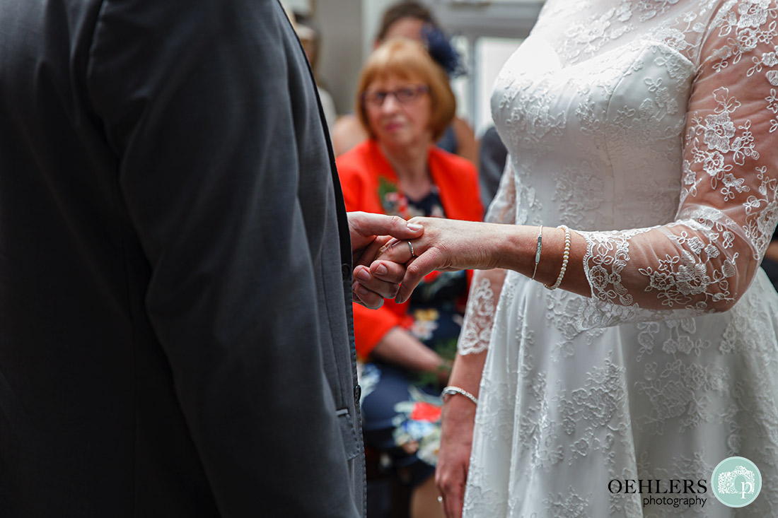 Kedleston Country House Photographers - close up of the bride's wedding ring being held by groom.