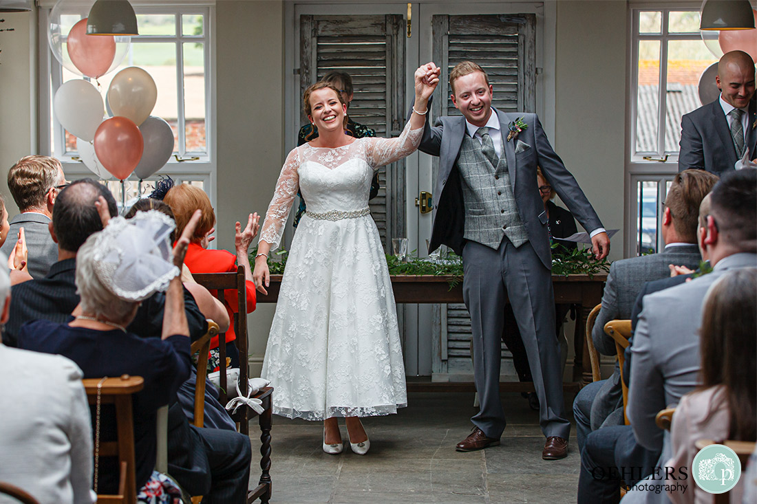 Kedleston Country House Photographers - bride and groom celebrating with hands held high before walking down the aisle.