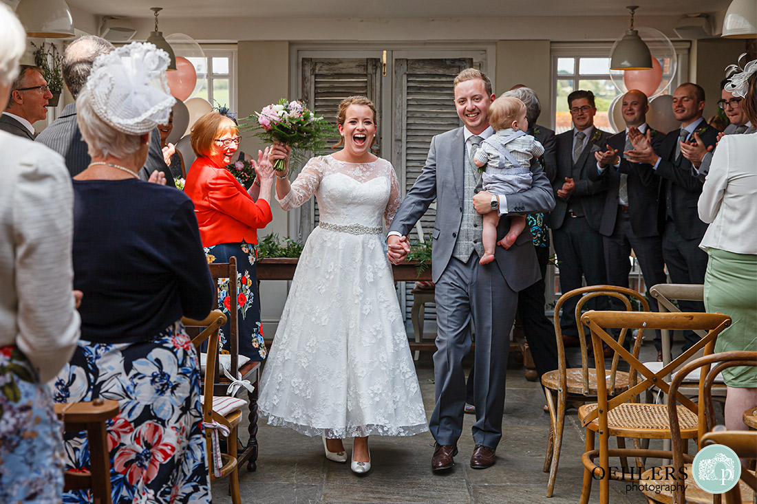 Kedleston Country House Photographers - happy couple walking down the aisle with their son in groom's arms.