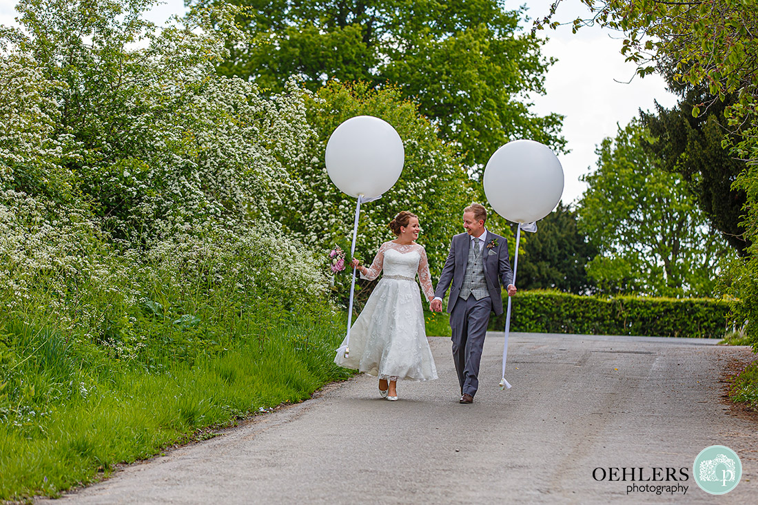 Kedleston Country House Photographers - bride and groom walking down a lane hand in hand carrying balloons.