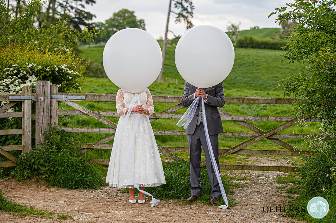 Bride and groom hiding behind the balloons.