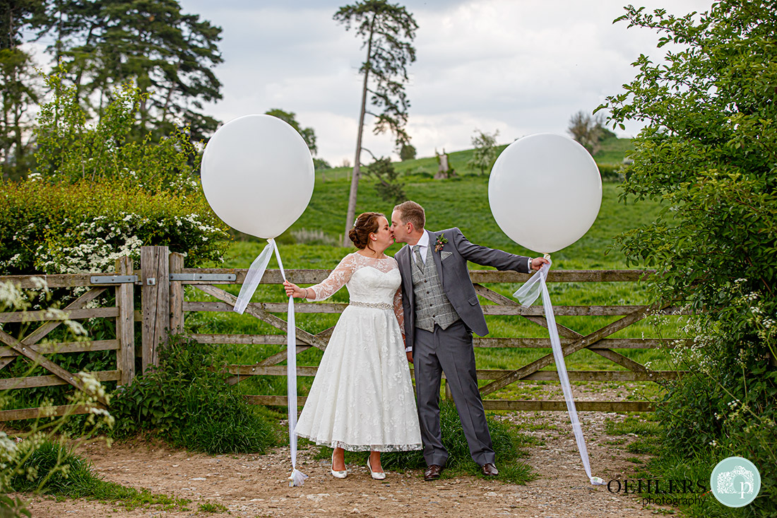 Kedleston Country House Photographers - couple kissing by a gate leading to a field holding balloons.